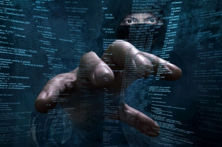 Hacker doing his thing in a balaclava - istock/gangis_khan